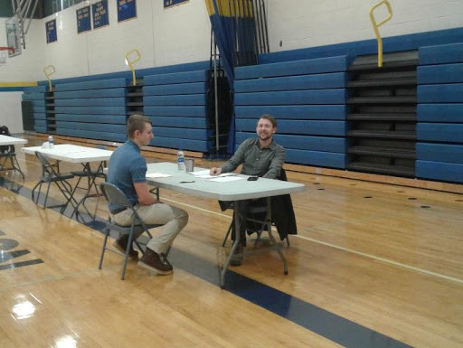 Metalfab Manufacturing's Kyle Yoder smiles for a photo while performing a mock interview with a Mio AuSable student.