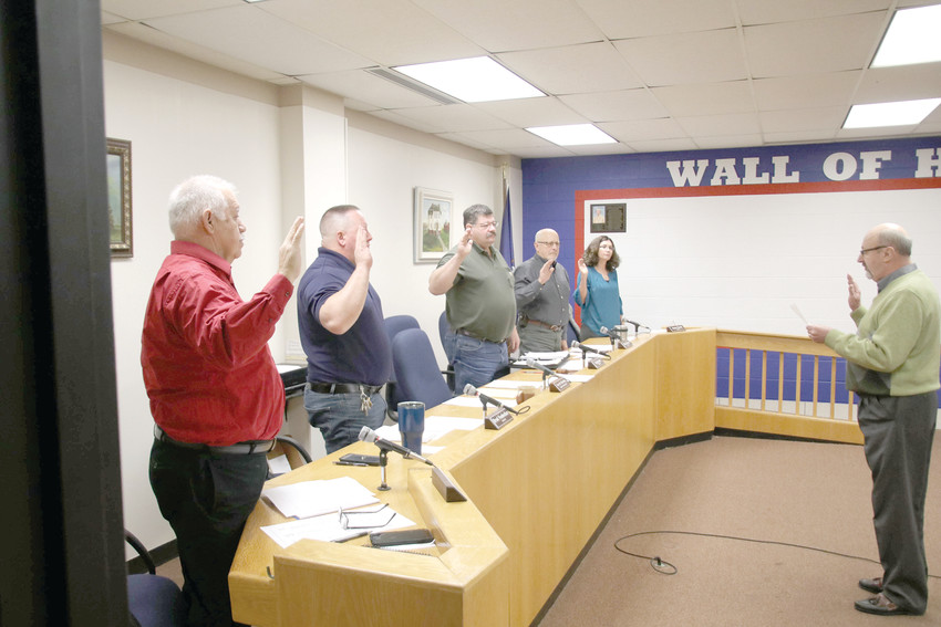 County Clerk Gary Klacking swears in the board of commissioners before the board's regular meeting Jan. 10. Look for an introduction to new Commissioners Ron Vaughn, Brad Neubecker and Jenny David in a future issue of the Herald.