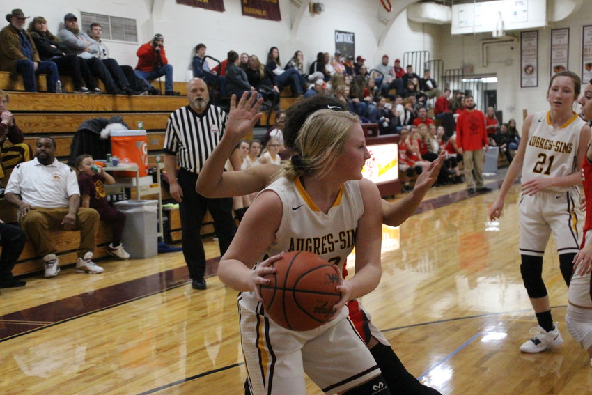 Au Gres' Kennadi Zeien clutches the ball at the baseline, looking for a pass.