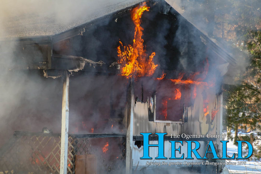 Flames rip through the front of the structure as fire crews gear up to battle the fire.