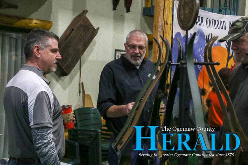 Mike Hoadley with Predator Bows, Mike Avery and Kelvin Ranney look over some of the bows Predator Bows has on display.