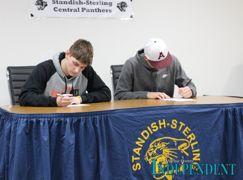 Dalton Neitzel signs his letter of intent to play football at Ohio Northern University, while Gage Nelson signs his letter of intent to play football at Alma College.