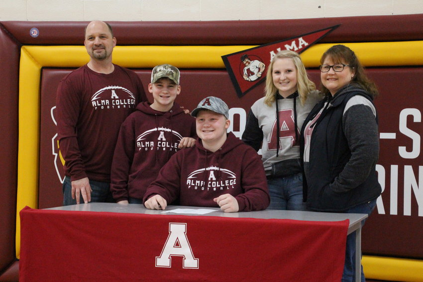 Chad, Carter, Kennadi and Karis Zeien pose with Caden after he committed to play football at Alma College.