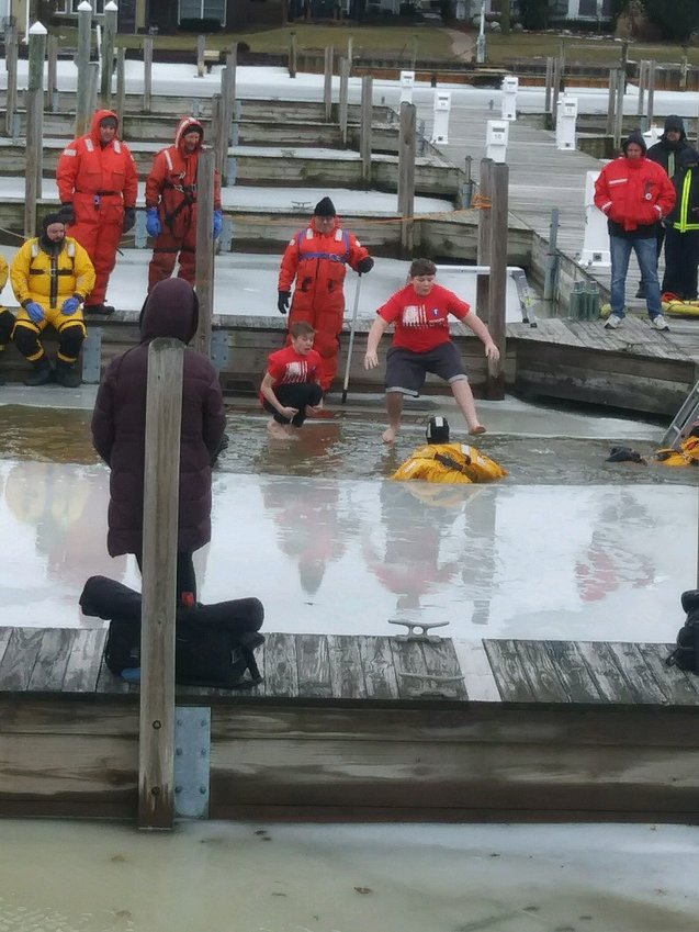 Gus and Will jump from the dock into the frigid water below for charity.