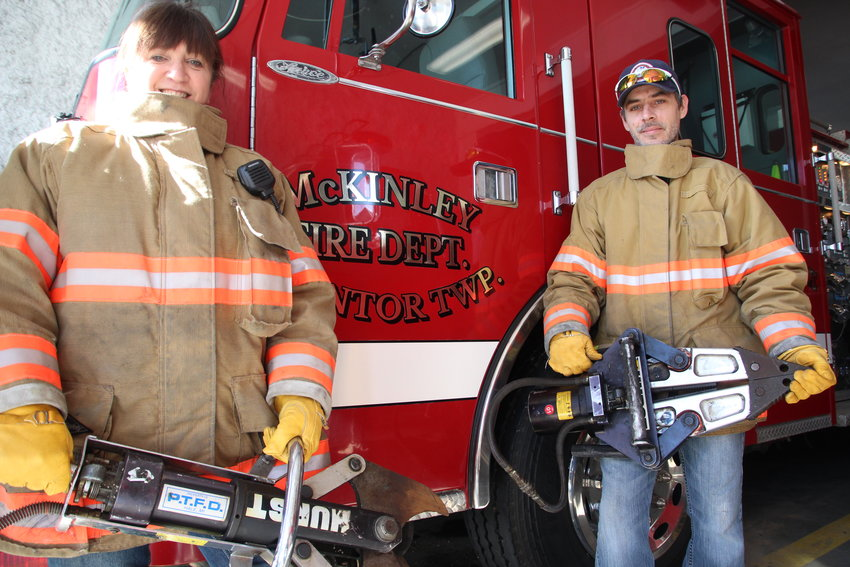 Firefighters Lori Walton and Cliff St. Onge hold the set of hydraulic shears recently donated from other departments.