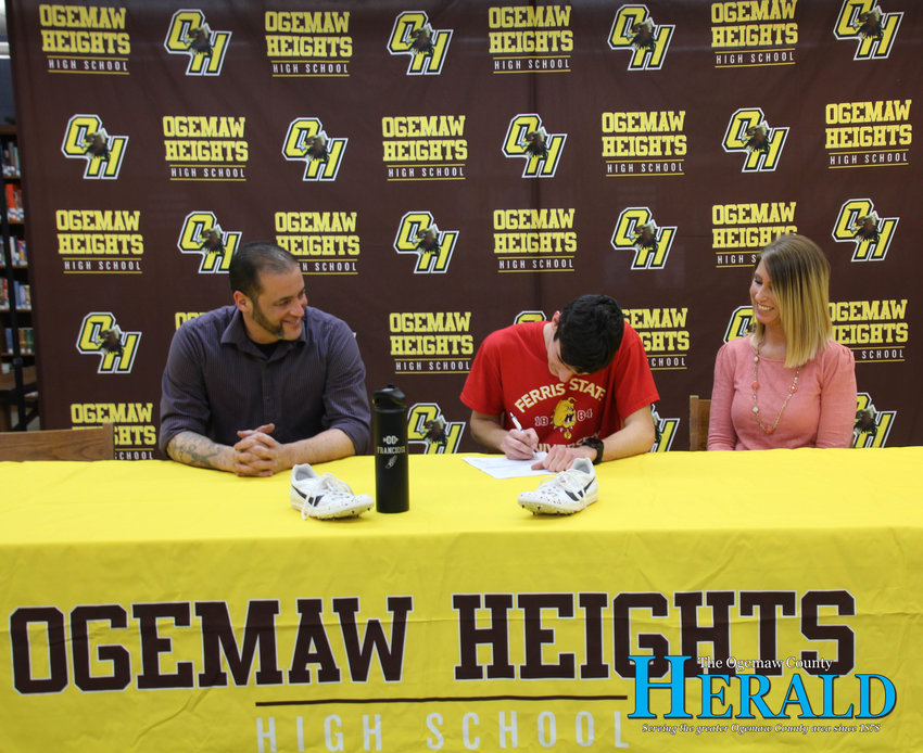 Derek Franciosi signs his letter of intent to run track and cross country at Ferris State University with his parents, Sam and Arianna Franciosi, by his side.