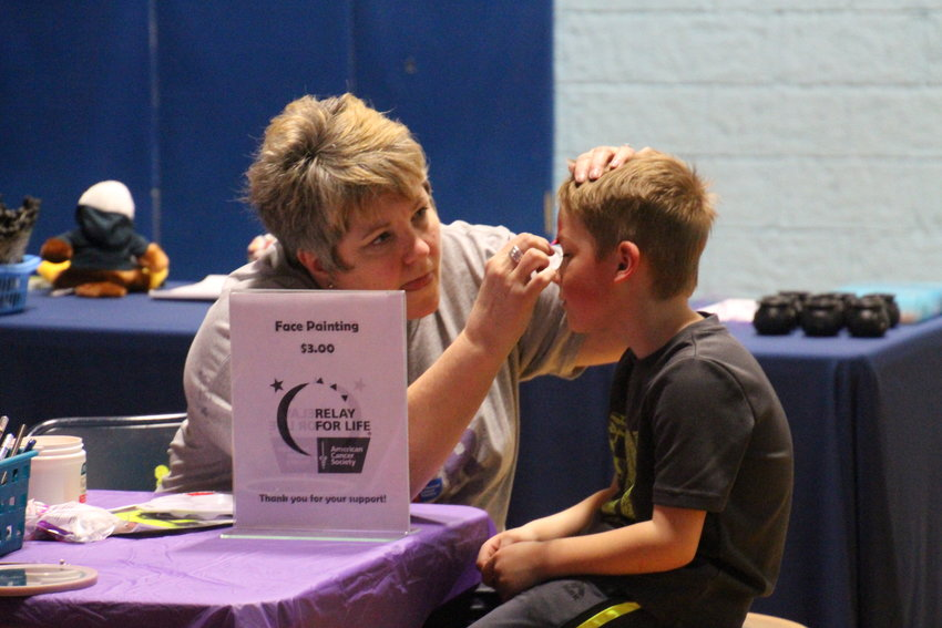 Cindy Augustine focuses while she works on an Iron Man face painting for Corbin Pomaville, 6.