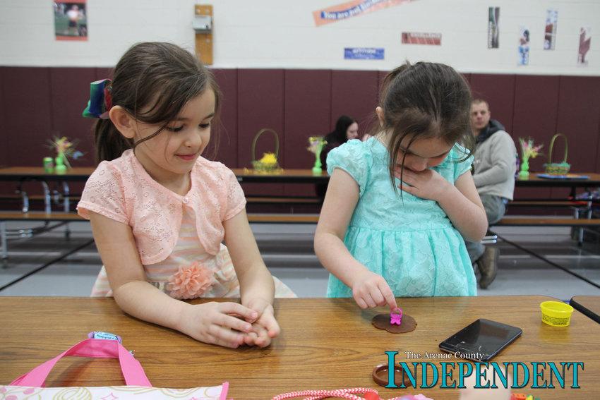 Sisters Alana, 6, and Jessica Sadlik, 4, of Au Gres play with playdough.