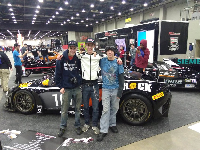 Devon Tappan of Fairview High School, Dylan Franciosi of Ogemaw Heights and George Martin of Fairview High School pose for a picture in front of a 2012 McLaren GT3 supercar.