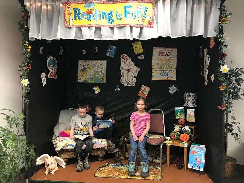 Children participate in the month-long reading contest by reading in the Dr. Seuss nook at the library.