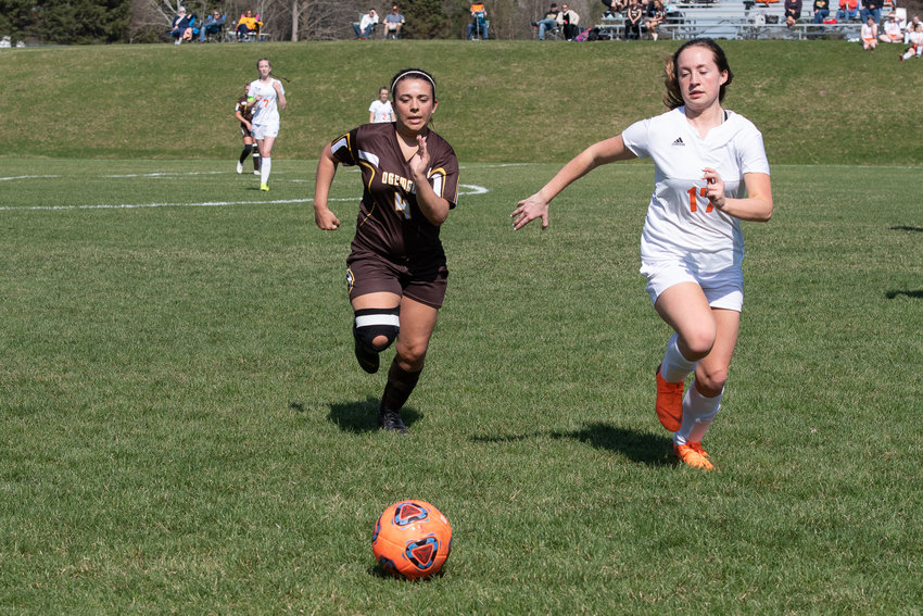 Lauren Zaske races Olivia Huber (17) to the soccer ball.