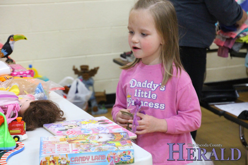 Kinsley Higgins, 5, of Fairview tries to decide which toy she wants to buy with her last dollar.