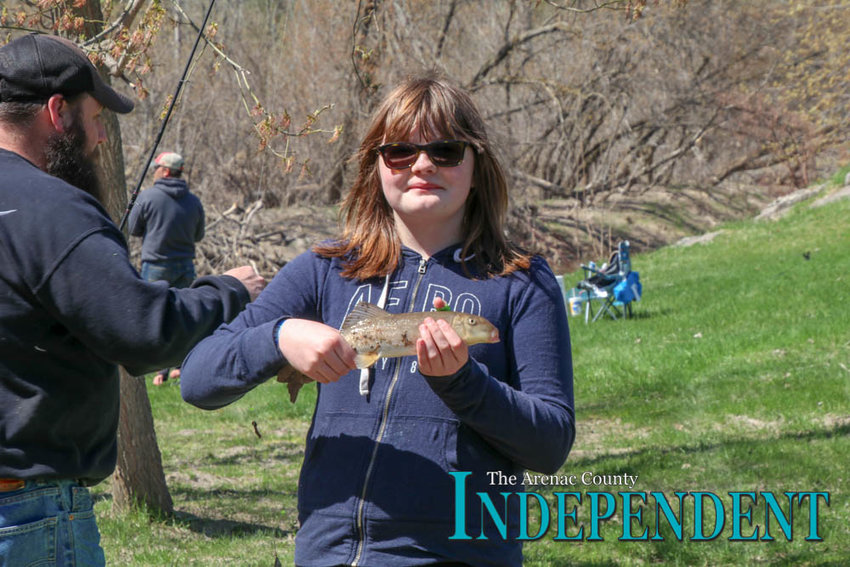 Maria Harrow, 11, poses with the first sucker taken along this stretch of the bank during the tournament.