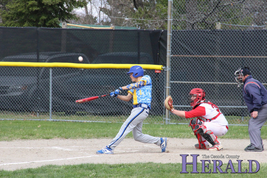 Mio's Brendan DeFlorio hits the ball while up to bat as W-P's Aaron Mervyn kneels behind as the catcher.