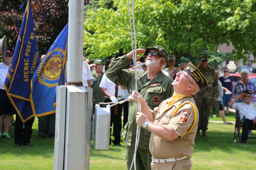 Jack Stodolak salutes as Charlie Rood lowers the flag after last year's Memorial Day parade in Standish.