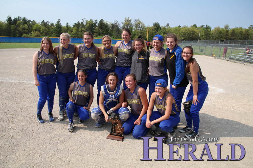 The Mio AuSable softball team poses for a photo with their trophy.
