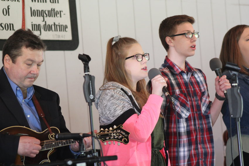 Emily and Josh Duty of Boyne City sing as Jeff Tuttle plays the mandolin.