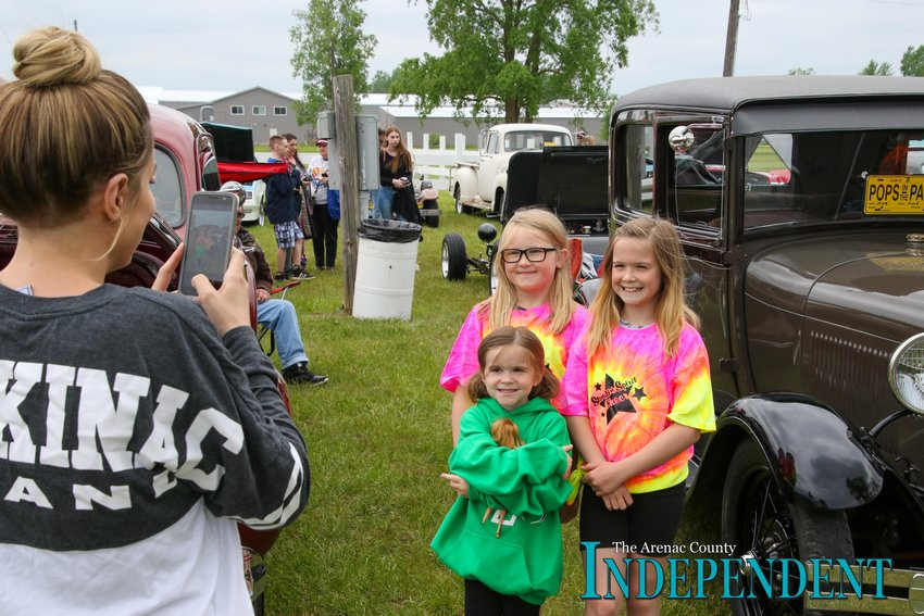 Amelia McConnell, 5, Carrington Sharp, 8, and Kaylee McConnell, 9, pose for a photo in front of one of the cars taken by Amelia and Kaylee's mom, Chelsie McConnell of Sterling.