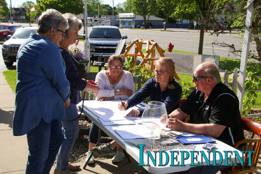 Volunteers Tammy Smith, Kim Osier and Wayne Lamrouex register Linda Proulx and Barb Osborne for bidding in the event.