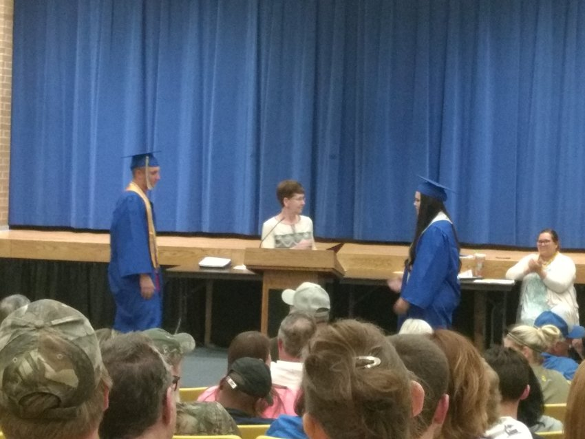 Chris Bush and Ashley Shaw approach Penny Irelan to accept their scholarships.