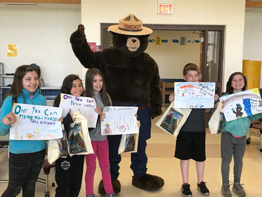 First-place Smokey Bear contest winner Olivia Wilt,  second-place Smokey Bear winner Rya Wiltse and honorable mention Smokey Bear contestant Cameron Gould pose with Smokey Bear, honorable mention Woodsy Owl contestant Grady Barringer and first-place Woodsy Owl winner Angellaya Burden. Not pictured is second-place Woodsy Owl contestant Kaitlyn Uren.