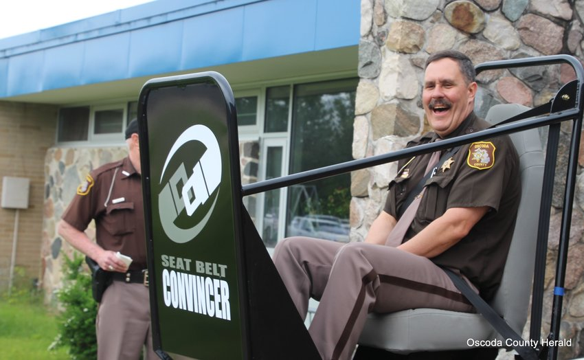 Sheriff Kevin Grace laughs after taking a ride in the Seat Belt Convincer.