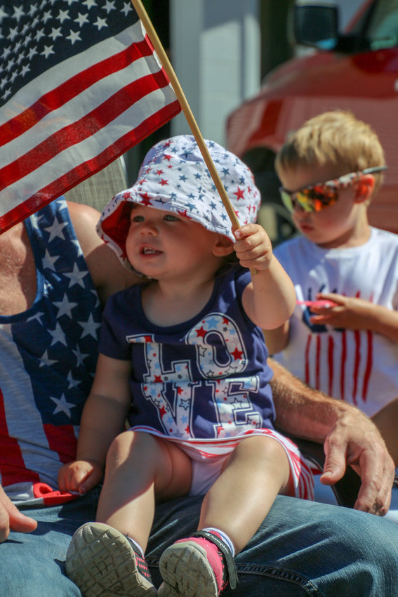 Lauren Golimbeski, 1 1/2 at the time, waves an American flag before the start of the 2018 Skidway Lake Independence Day Parade July 7.