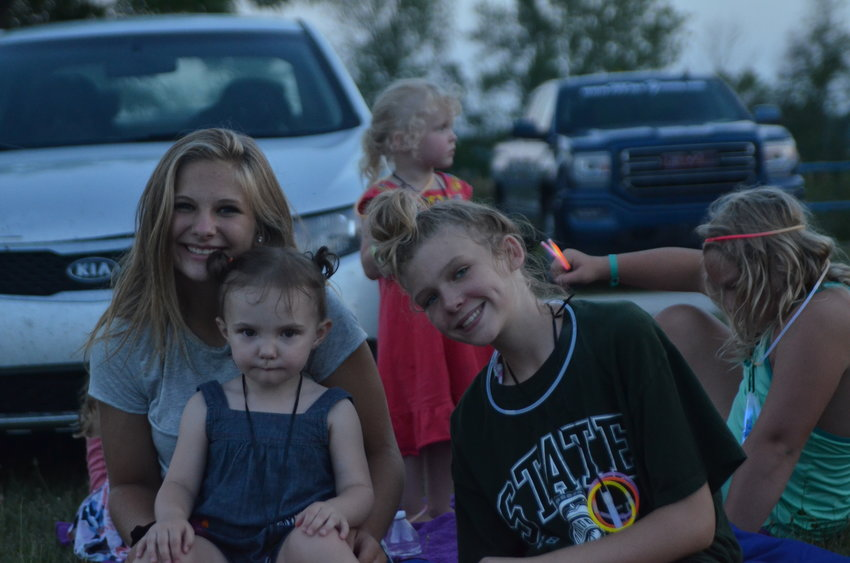 Keagen Skacal, Aurora Denny and Keira Esslin pose for a photo before the fireworks begin in Au Gres last year.