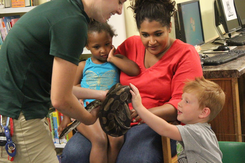 Jackson Zanon, 3, is excited to pet the snake Megan Burkhart holds out, as Izabelle, 3, and Elizabeth Williamson watch.