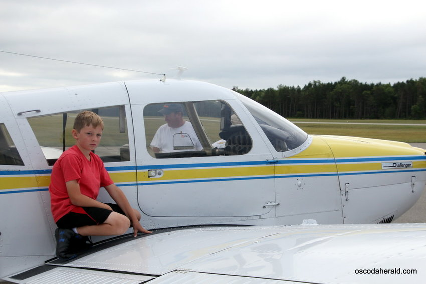 Xander Russell, 10 at the time, of Romeo kneels on the wing of a 1973 Piper Cherokee 180 owned by his grandpa, Greg Hill, at a past fly-in event.