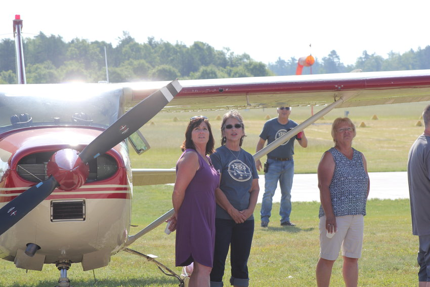 Amy Solak of Traverse City and Jeannie Antcliff of West Branch, middle, watch a plane pass by.