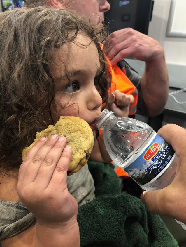 After being lost for more than 24 hours, Gabriella Vitale takes a break from eating a cookie for a sip of water.