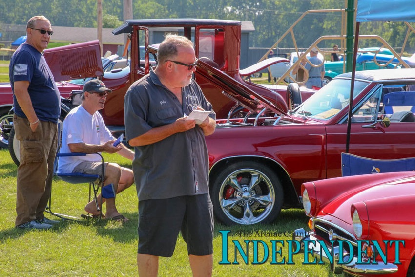 John Nelson of Redford fills out his ballot card as he admires a couple classic rides during last year's event.