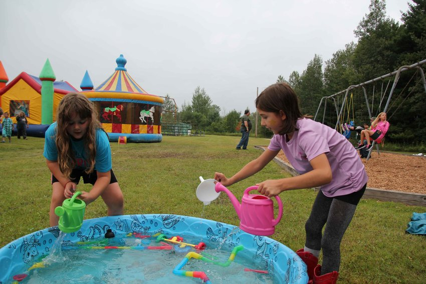 Cydney Madigan, 7, and Reagan Satkowiak, 8, play with water.