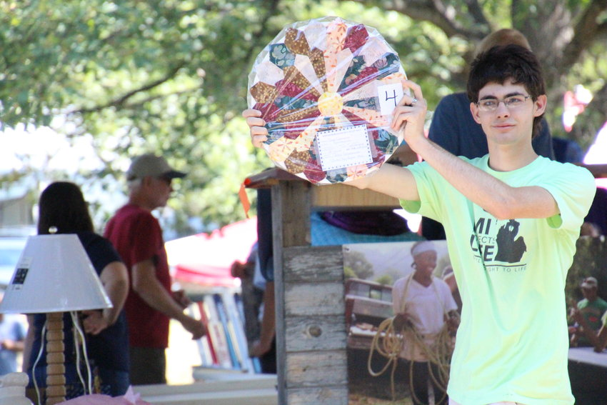 A young man holds up a circular quilted wall hanging during the quilt auction.