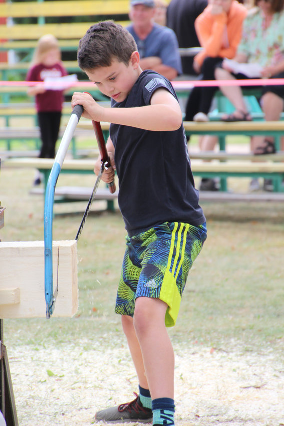 Gabe Helsel pushes through a log as he participates in a competition.