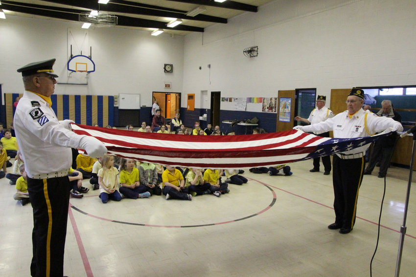 Mike Thorne and Sheldon Justice unfurl an American flag as they demonstrate an honor guard ceremony to kids at St. Joe's in 2016.