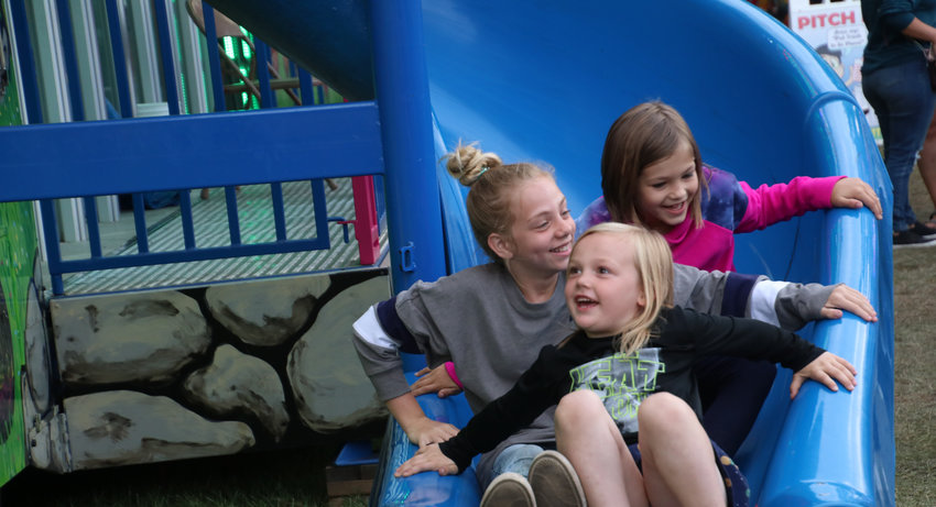 From front to back, Vanessa Sholes, Addison Harley and Annabelle Sholes head down the slide together at the fair.