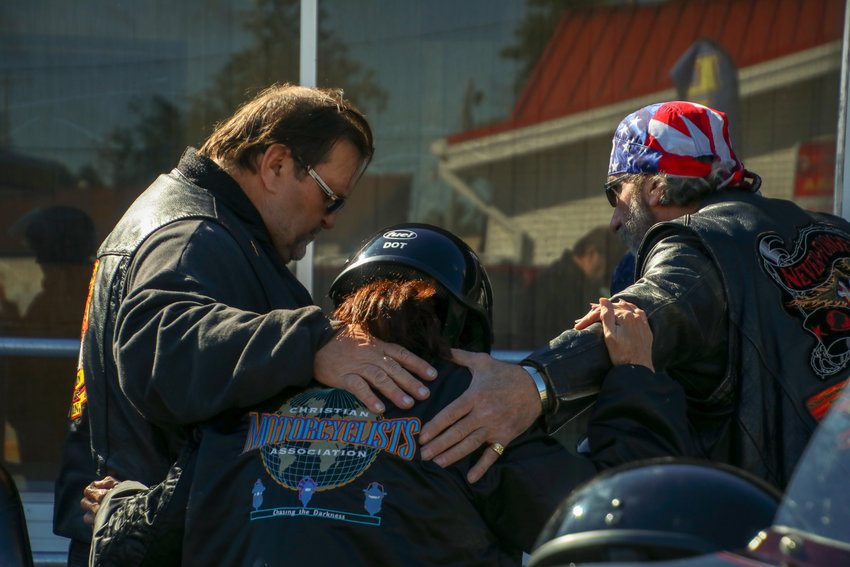 Bikers bow their heads in prayer before the ride.