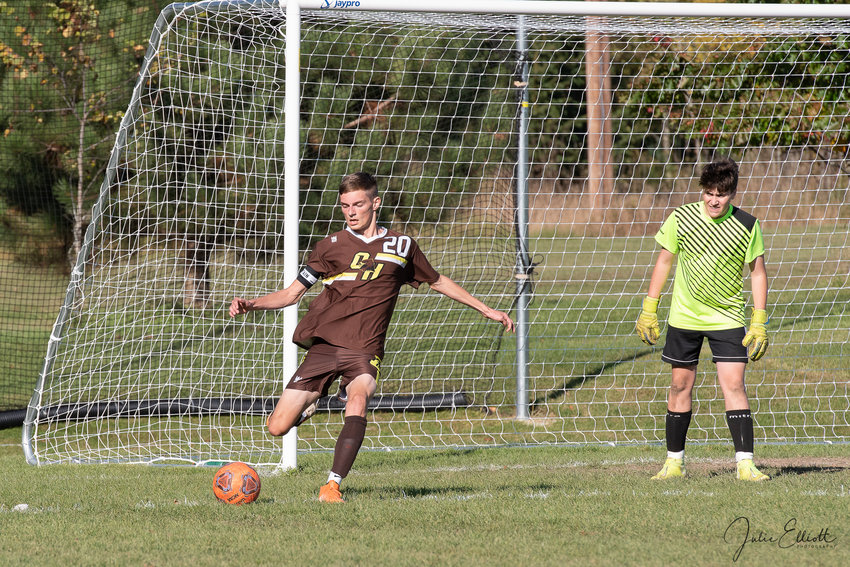 Alex Kennedy takes the goal kick for the Falcons while keeper Jake Bonus looks on.