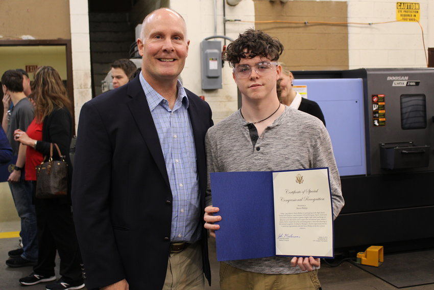 Ogemaw Heights student Aaron Phillips poses holding his Congressional certificate next to U.S. Rep. John Moolenaar.
