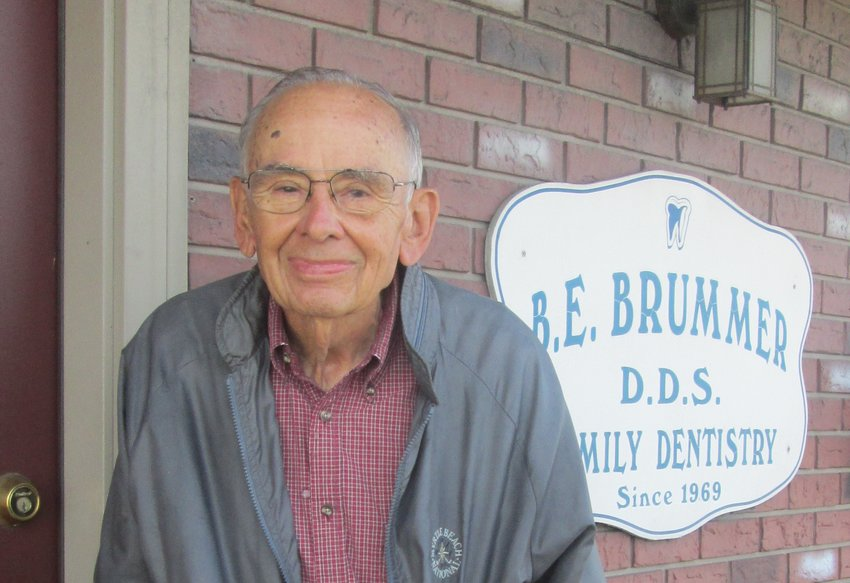 Dr. Benjamin Brummer stands in front of his practice on his last day before retirement.