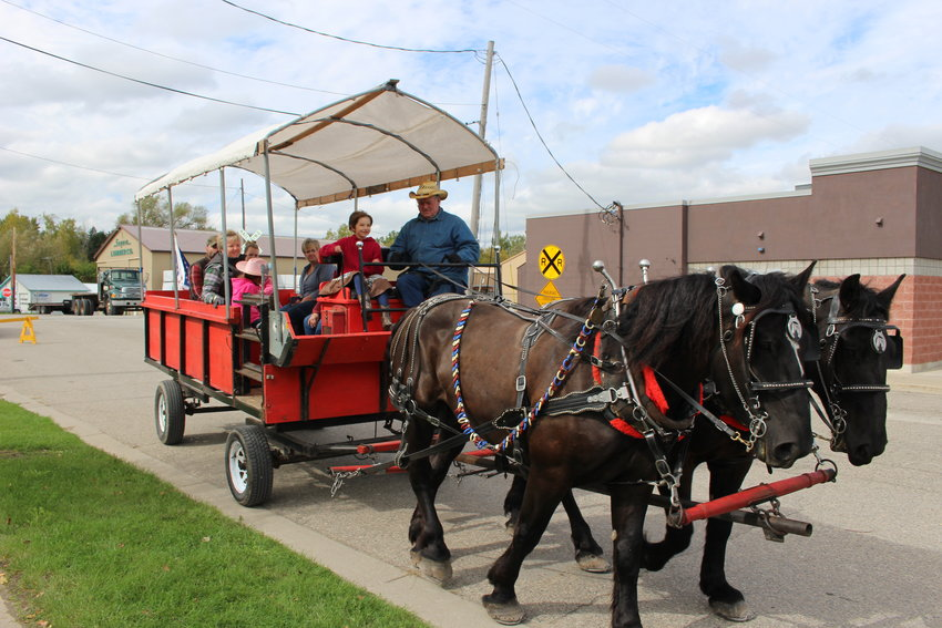 Paul Mier of Alger drives a horse-drawn carriage with the help of Bindi Senske, 9, of Prescott.