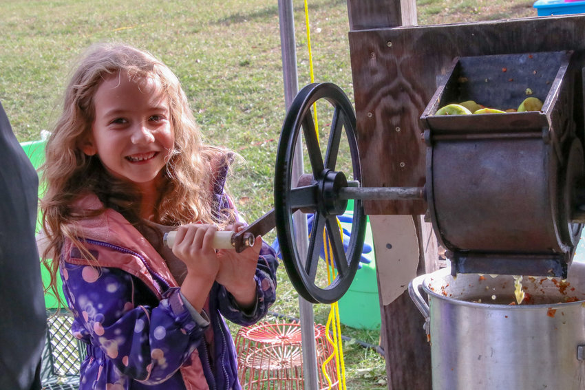 Arcadia Burgei of Fairview smiles as she works the cider press.