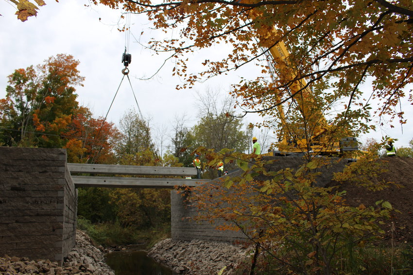 Workers begin laying the deck on the bridge.