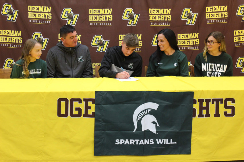 Tyler Eedy's family watches as he signs his National Letter of Intent.