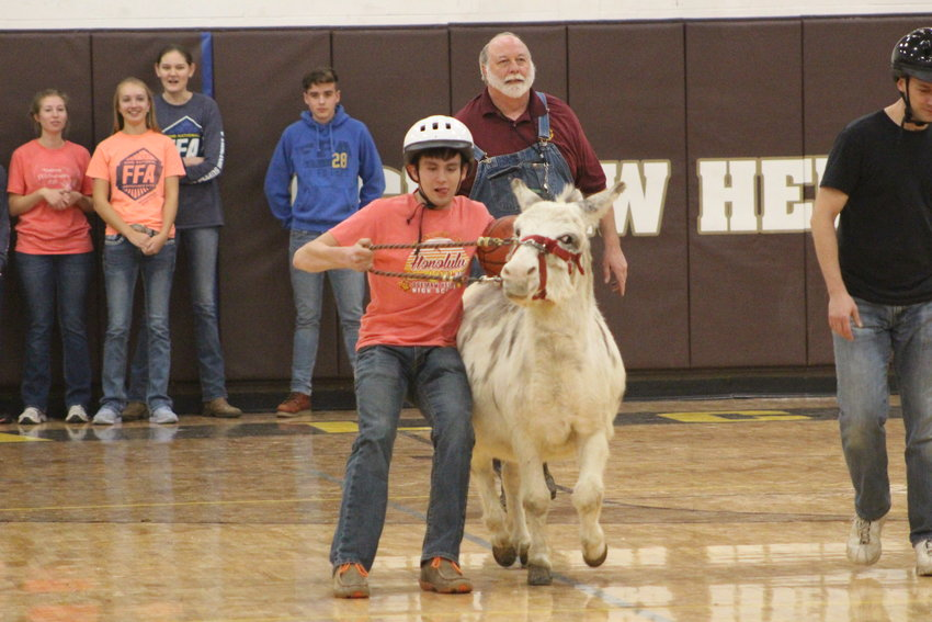 Zachary Daniels slides across the gym while trying to reign in his donkey.