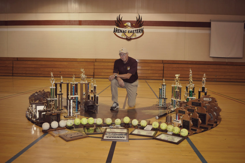 Arenac Eastern softball coach Mike Vogl posing with all the awards won by the team in the AE gymnasium.