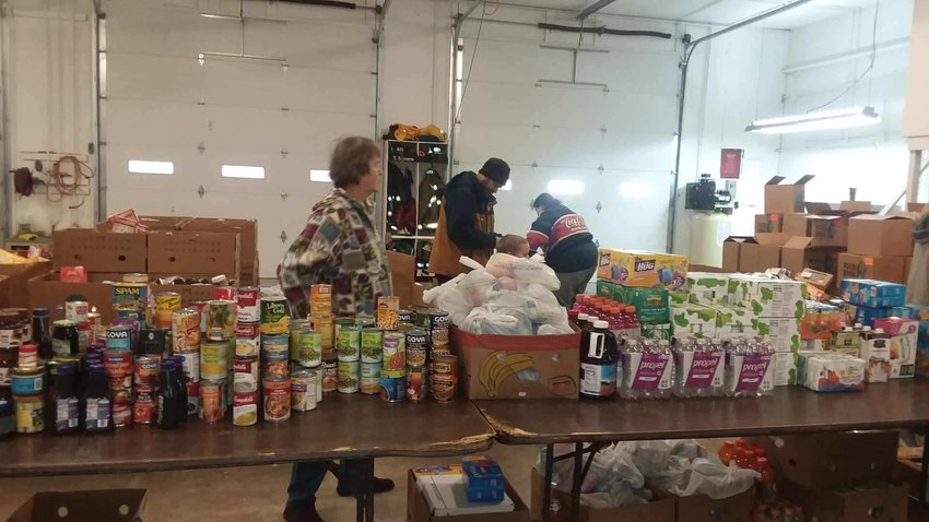 Food pantry volunteers keep the line well-stocked during a giveaway at the Mills Twp. Fire Department.
