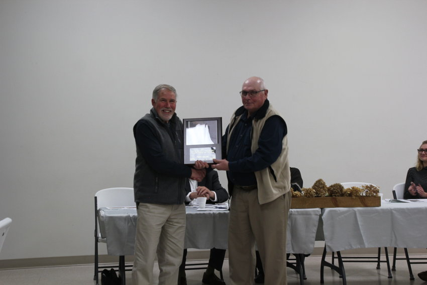 Earl Steinbauer presents Terry Collier with the conservationist of the year award.